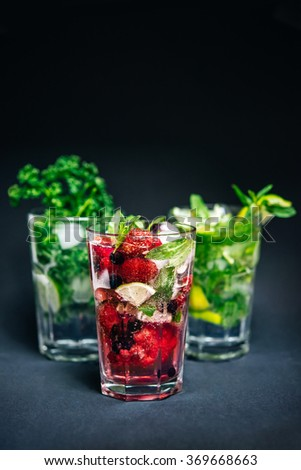 Different types of mojito cocktail on dark background