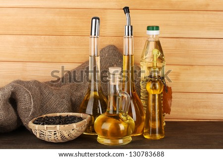 Different types of oil with sunflower seeds on wooden background