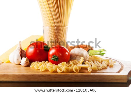 Different types of pasta and vegetables on wooden board