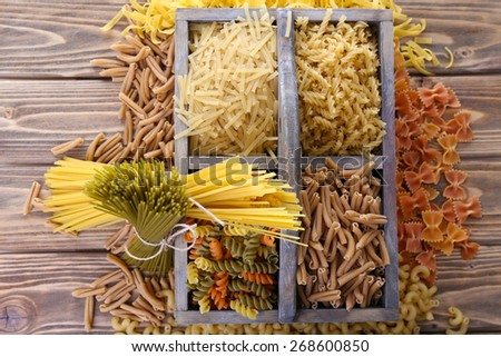 Different types of pasta in box on wooden background - stock photo