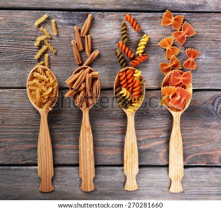 Different types of pasta in spoons on wooden background - stock photo