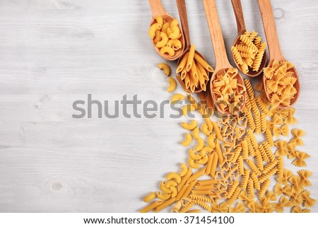 Different types of pasta lying in wooden spoons lying like a frame on white wooden table. Gomiti rigati, penne, heart-shaped pasta, fuzilli, and farfalle. - stock photo