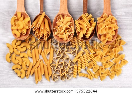 Different types of pasta lying in wooden spoons lying on white wooden table. Gomiti rigati, penne, heart-shaped pasta, fuzilli, and farfalle. - stock photo