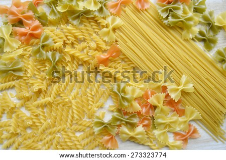 Different types of pasta, macro view on a wooden table - stock photo