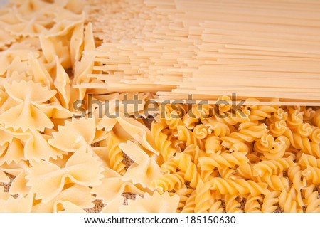 Different types of pasta on a linen background