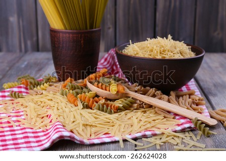 Different types of pasta on napkin on wooden background - stock photo
