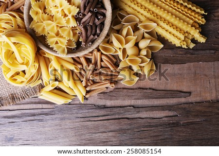 Different types of pasta on rustic wooden table - stock photo