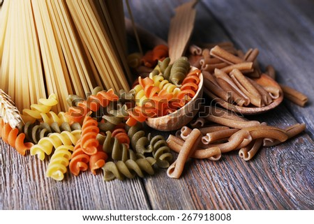 Different types of pasta on wooden background - stock photo