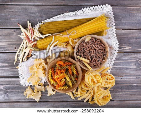Different types of pasta on wooden planks background - stock photo