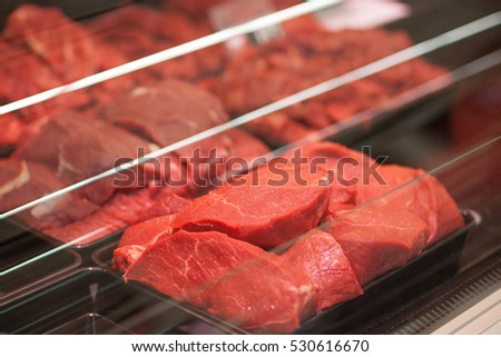 Different types of raw meat in plastic boxes in supermarket