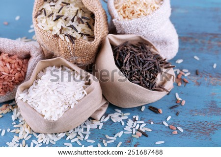 Different types of rice in sacks on wooden background - stock photo