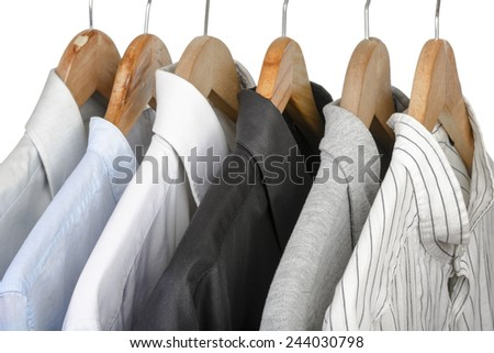 Different types of shirts on wooden hangers. Selective focus.