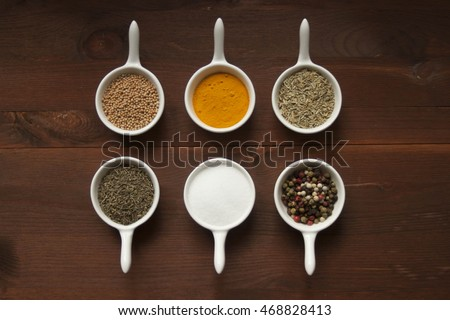 Different types of spices in small, porcelain bowls on a wooden surface