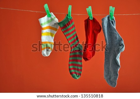 Different types of striped socks hanging on a rope isolated on red - stock photo