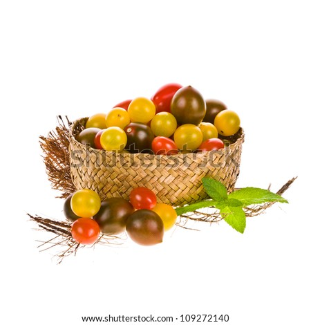 different types of tomatoes, cherry tomatoes, yellow, red and kumato in a wicker basket isolated on white background
