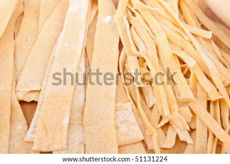 Different Types of Uncooked Homemade Egg Pasta on a Cutting Board - stock photo