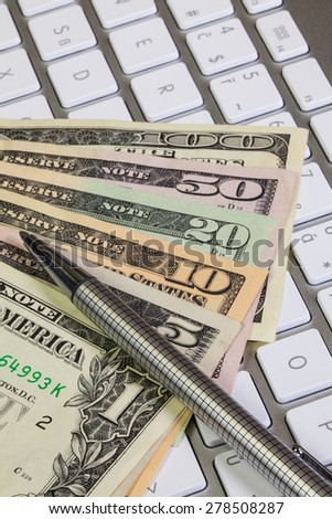 Different US dollar banknotes and pencil on the keyboard