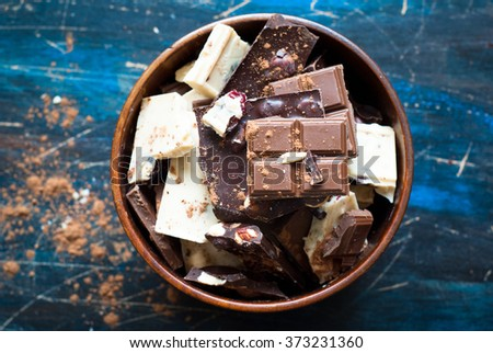 Different varieties of chocolate. White chocolate with hazelnuts and cranberries, milk and dark chocolate with hazelnuts in a wooden bowl on the table. - stock photo