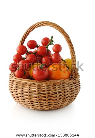 Different varieties of tomatoes in a basket on a white background