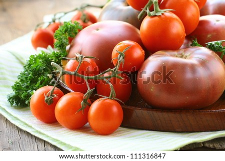 different varieties of tomatoes on wooden plate