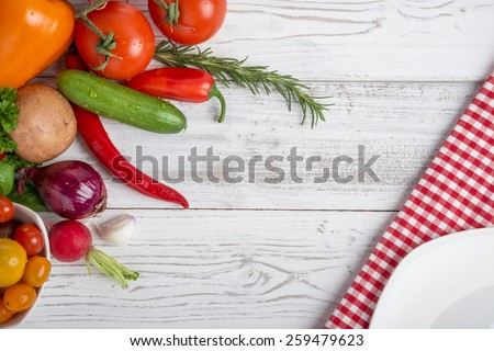 different vegetables and herbs on wood, plate and kitchen towel, copy space