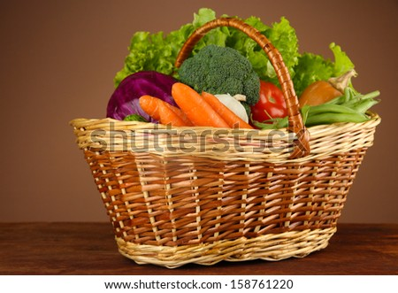 Different vegetables in basket on table on brown background - stock photo