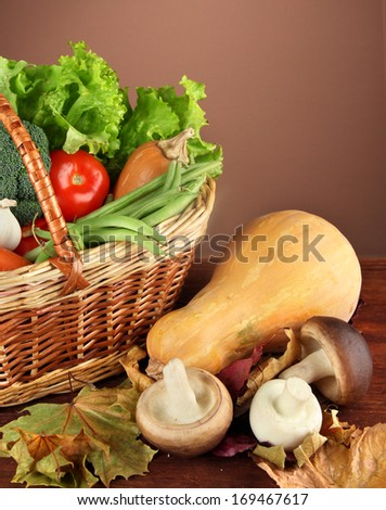Different vegetables in basket with yellow leaves on table on brown background