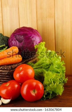 Different vegetables on basket on table on wooden background - stock photo