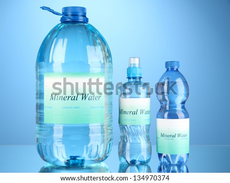 Different water bottles with label on blue background
