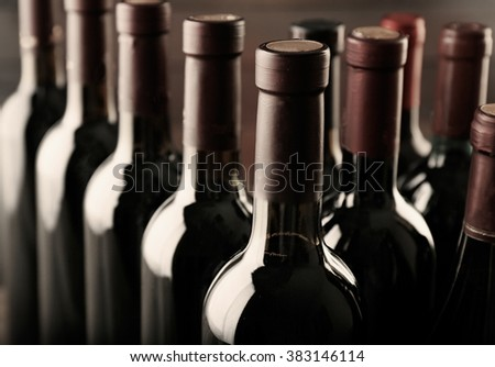 Different wine bottlenecks on dark background - stock photo