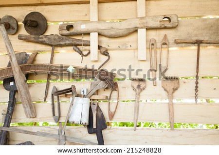 Different wooden tools for household works hanging on wall - stock photo