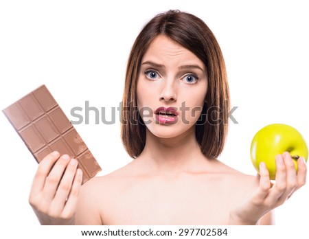 Difficult decision. Worried shirtless woman choosing between chocolate and  apple. Healthy lifestyle concept. - stock photo