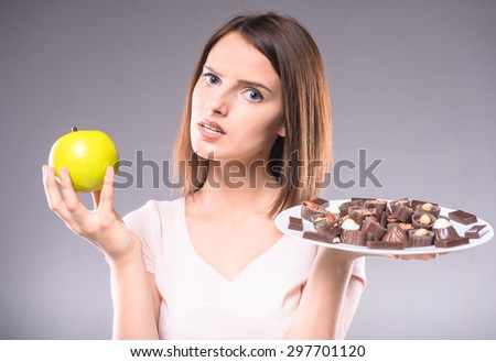 Difficult decision. Worried woman choosing between chocolates and  apple. Healthy lifestyle concept. - stock photo