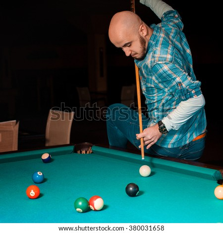 difficult hit is preparing to perform a player on the pool table. American pool billiard. Pool billiard game. Billiard sport concept. - stock photo
