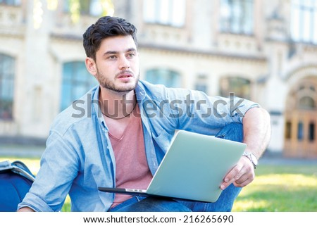 Difficult university. Cute male student holding a laptop and reading a book and looking away while sitting on the grass near the campus of the University at the break. - stock photo