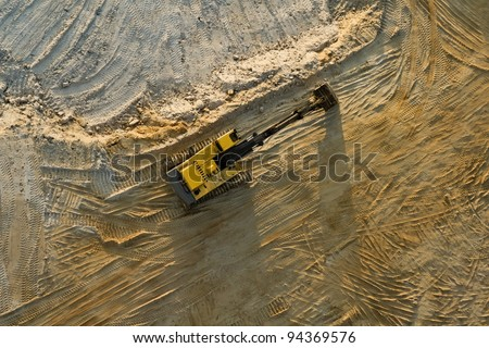 Digger in sand quarry from an aerial view - stock photo