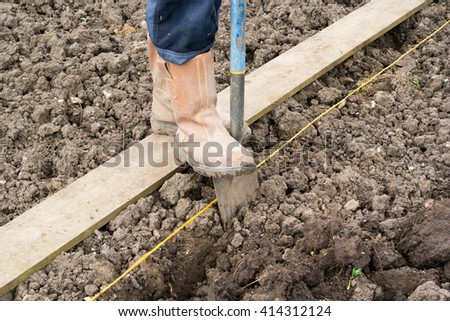 Digging over soil on an allotment - stock photo