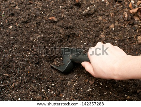 Digging soil with black gardening tool - stock photo
