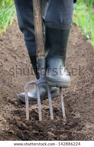 Digging spring soil with shovel - stock photo