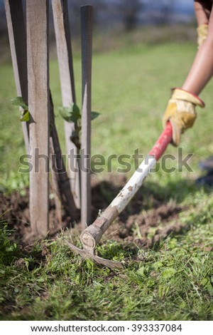 Digging the garden soil with hoe - stock photo