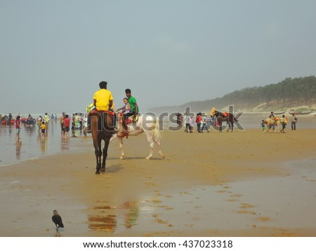 Digha, India - June 11, 2016: People riding horse on sea beach