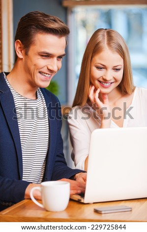 Digital age couple. Beautiful young loving couple bonding to each other and looking at the laptop while sitting in cafe together  - stock photo