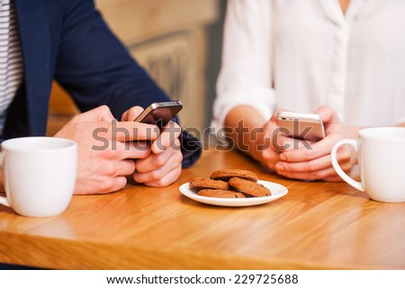 Digital age couple. Close-up of couple texting on their mobile phones while sitting together in cafe  - stock photo
