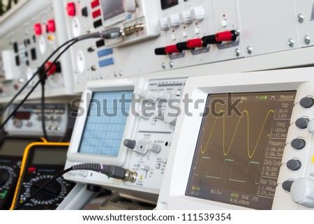 digital and analog oscilloscope in the foreground, in the background measuring devices with cables ready for measurements in electrical laboratory