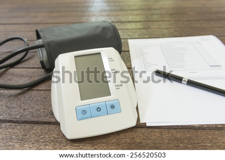 Digital blood pressure monitor on a wood table.