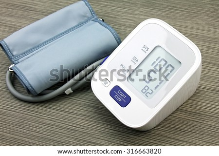 Digital Blood Pressure Monitor on wood background, Medical and Examining equipment.