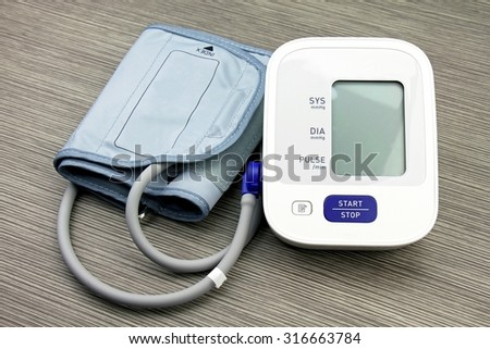 Digital Blood Pressure Monitor on wood background, Medical equipment, Examining equipment. - stock photo