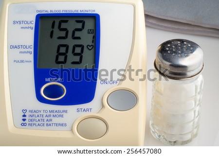 digital blood pressure monitor with salt shaker - stock photo