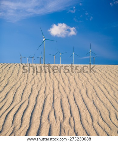 Digital composite image of large wind turbines with a blue sky and clouds over rippling sand dunes. - stock photo