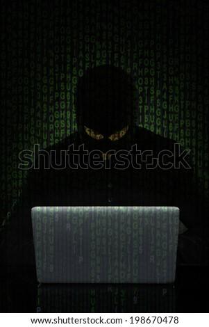 Digital composite image of man wearing balaclava hacking laptop at desk - stock photo